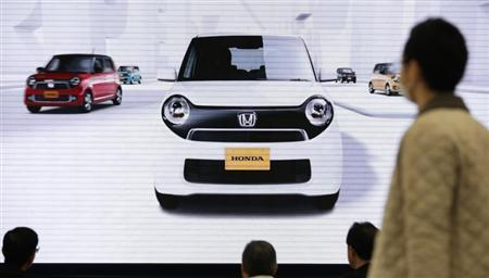 Visitors look at a screen showing Honda Motor's minicar ''N-ONE'' series at the company's showroom in Tokyo January 31, 2013. REUTERS/Issei Kato