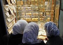Женщины рассматривают золотые украшения на витрине ювелирного магазина в Дамаске 17 апреля 2012 года. Цены на золото стабильны, так как улучшение экономических показателей США снижает его привлекательность как надежного вложения. REUTERS/Khaled al-Hariri