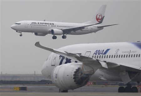A Japan Airlines aircraft (above) approaches for landing as an All Nippon Airways' Boeing Co's 787 Dreamliner plane parks on the tarmac at Haneda Airport in Tokyo February 4, 2013. REUTERS/Toru Hanai