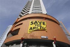 """Los planes de los países del Ártico para empezar a cooperar en vertidos son vagos y no definen las obligaciones corporativas en caso de accidente en una región helada que se abre a la exploración gasística y petrolera por el calentamiento global, dijeron el lunes los ecologistas. En la imagen, varios activistas econologistas cuelgan un cartel en el que se lee """"Salvemos el Ártico"""" en Moscú el 17 de abril de 2012. REUTERS/Denis Sinyakov"""