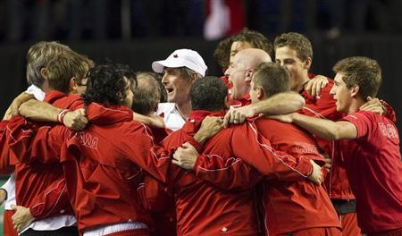 Team Canada's head coach Martin Laurendeau (white cap) celebrates with his team after Canada's Milos Raonic defeated Spain's Guillermo Garcia-Lopez with teammates during the final round of the Davis Cup tennis tie in Vancouver, British Columbia February 3, 2013. REUTERS/Ben Nelms