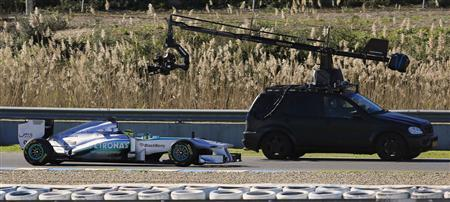 Mercedes Formula One driver Nico Rosberg of Germany rides the new Mercedes W04 Formula One car around the track next to a camera mounted on a car before its official presentation at the Jerez racetrack in southern Spain February 4, 2013. REUTERS/Marcelo Del Pozo