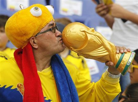 A Colombia fan kisses a replica of the World Cup trophy before their 2014 World Cup qualifying soccer match against Paraguay in Barranquilla, October 12, 2012. REUTERS/Joaquin Sarmiento (COLOMBIA - Tags: SPORT SOCCER)