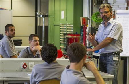 Siemens engineering apprentices listen to a teacher (R) during a class at the Siemens training centre in Berlin, August 30, 2012. Siemens has enrolled 29 students from 14 European countries for the ''Europeans at Siemens'' program to teach them in the sectors of mechatronics and engineering. After completing the three-and-a-half-year program they will be eligible to pass exams that are recognized by the German Chamber of Commerce. REUTERS/Thomas Peter (GERMANY - Tags: EDUCATION BUSINESS EMPLOYMENT)