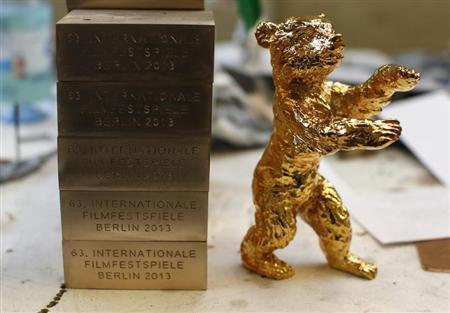 A golden Berlin Bear award for the upcoming 63rd Berlinale International Film Festival is pictured next to labels on a working desk at the Noack foundry in Berlin January 30, 2013. REUTERS/Fabrizio Bensch