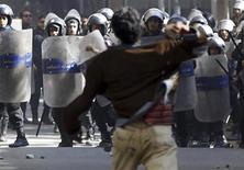 Un opositor al Gobierno del presidente de Egipto, Mohamed Mursi, lanza una piedra contra unos policías durante el funeral de los activistas Mohamed al-Gendy y Amr Saad en El Cairo, feb 4 2013. La principal alianza de oposición de Egipto quedó envuelta el lunes en una confusión por aparentemente respaldar un llamado a derrocar al presidente islamista Mohamed Mursi y luego retractarse. REUTERS/Amr Abdallah Dalsh