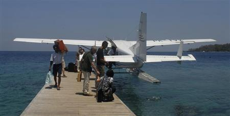 Tourists feed reef fish after getting off a seaplane at Moyo Island in eastern Indonesia September 19, 2012. REUTERS/Neil Chatterjee