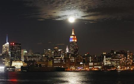 A full moon rises behind the Empire State Building and the skyline of New York, as seen from a park along the Hudson River in Hoboken, New Jersey, December 28, 2012. REUTERS/Gary Hershorn