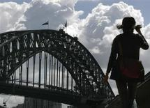 A tourist walks towards the Sydney Harbour Bridge at Circular Quay September 24, 2008 as clouds form in the distance. REUTERS/Will Burgess