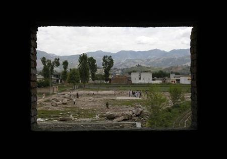 Children are seen through the window of a house under construction as they play cricket on the demolished site of a compound of Osama bin Laden in Abbottabad May 1, 2012. REUTERS/Mian Khursheed