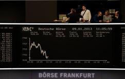 Las bolsas europeas sufrieron profundas caídas el lunes, en medio de una creciente incertidumbre política en los países de la periferia de la zona euro, que llevó a los inversores a recoger beneficios en mercados que estaban operando cerca de máximos de varios años. En la imagen, gente en el balcón sobre la pantalla del índice DAX en la Bolsa de Fráncfort, el 9 de enero de 2013. REUTERS/Remote/Lizza David
