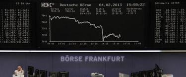 A trader speaks on a phone as he stands below the DAX board at the Frankfurt stock exchange February 4, 2013. REUTERS/Remote/Janine Eggert (GERMANY - Tags: BUSINESS)