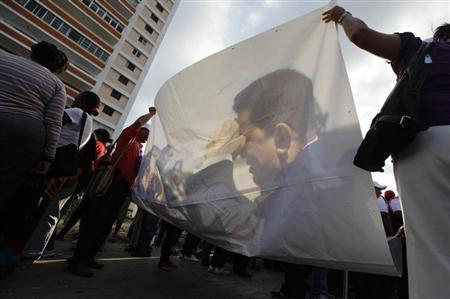 Venezuelan students carry a picture of President Hugo Chavez during a gathering in show of support in Havana February 4, 2013. REUTERS/Desmond Boylan