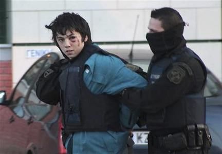 A policeman escorts suspected bank robber Nikolaos Romanos at prosecutor's office in Kozani town in northern Greece February 3, 2013. REUTERS/Eurokinissi