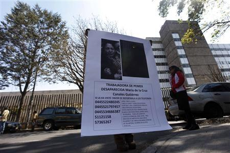 A woman holds a poster of Maria de la Cruz Canales Gutierrez, a Pemex employee who has been missing since an explosion at the headquarters of state-owned oil giant Pemex, outside Pemex hospital in Mexico City February 4, 2013. REUTERS/Edgard Garrido