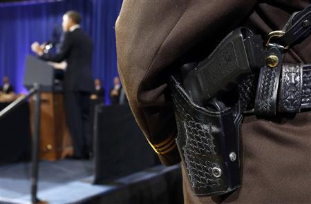 A police officer's gun sits in its holster as U.S. President Barack Obama speaks about ways to reduce gun violence during a visit to the Minneapolis Police Department Special Operations Center in Minneapolis, Minnesota February 4, 2013. REUTERS/Kevin Lamarque (UNITED STATES - Tags: POLITICS CRIME LAW)