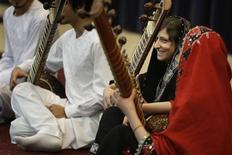 A girl smiles after playing the sitar during a performance by members of the Young Afghan Traditional Ensemble at the State Department in Washington, February 4, 2013. REUTERS/Jonathan Ernst