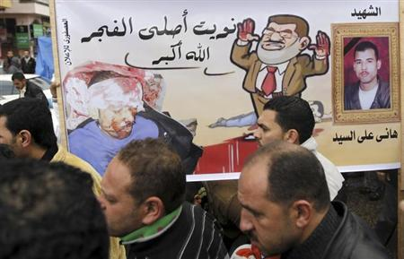 Protesters opposing Egyptian President Mohamed Mursi walk near a poster, of him and Hany Aly El Said, before an anti-Mursi demonstration in Port Said February 1, 2013. El Said was killed in Port Said demonstrations last week. The words on the poster read ''I will pray Al Fajr prayers.'' REUTERS/Amr Abdallah Dalsh