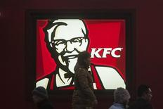 People walk past a KFC restaurant in Shanghai, China in this January 17, 2013 file photograph. KFC parent Yum Brands Inc on Monday reported a 6 percent drop in fourth-quarter sales at established restaurants in China after a food safety scare ensnared some of its chicken suppliers in its top market. REUTERS/Aly Song/Files