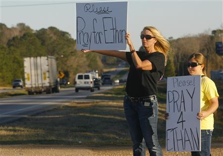 Sherry Johnson Parker and her daughter Olivia Parker hold signs along Highway 231 asking drivers to pray for Ethan, a 5-year-old boy taken hostage five days ago, after a bus driver was shot and killed near Midland City, Alabama February 3, 2013. REUTERS/Phil Sears