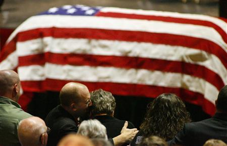 Aaron Poland, son of murdered bus driver Charles Albert Poland Jr., hugs and kisses his mom Mary Janice Poland moments after the casket containing Poland Jr.'s body is presented at Ozark Civic Center, near Midland City, Alabama, February 3, 2013. REUTERS/Phil Sears