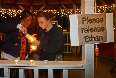 Mileah Lomaneck and Whitley Riley light candles during a candlelight vigil at City Hall in Midland City, Alabama, January 31, 2013. The vigil honored the memory of bus driver Charles Poland, and showed support for the release of a five-year-old boy held hostage in a bunker by Poland's alleged killer. REUTERS/Phil Sears