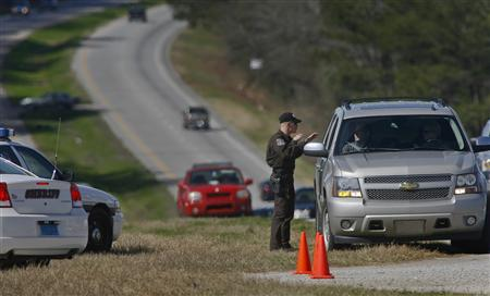 A Dale County Alabama Sheriff's deputy talks to a driver at a roadblock near the scene of a shooting and hostage taking near Midland City, Alabama February 1, 2013. REUTERS/Phil Sears (UNITED STATES - Tags: CRIME LAW)
