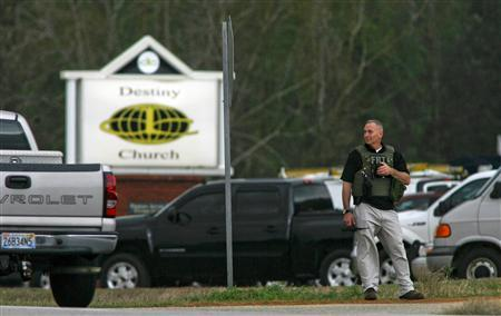 An FBI official stands at a roadblock near Destiny Church, the scene of a shooting and hostage taking, in Midland City, Alabama, January 30, 2013. A gunman boarded an Alabama school bus ferrying children home from school on Tuesday and fatally shot the driver before fleeing with a young child and holing up in an underground bunker, Alabama media reported. Sheriff's officials confirmed that one person had been killed in a shooting involving a school bus in Alabama's Dale County but gave scant details other than to say that a child was present at the scene in Midland City. REUTERS/Phil Sears