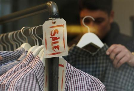 A man looks at clothes on a Sale rail inside a shop during the Christmas sales in London December 27, 2012. REUTERS/Luke MacGregor