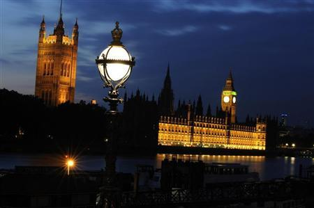 The Houses of Parliament (R) are seen on the bank of the River Thames at night in central London, June 21, 2009. REUTERS/Nigel Roddis