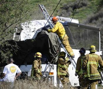 San Bernardino firefighters start the final process of removing the body of a victim trapped in a bus on Highway 38, north of Yucaipa, California February 4, 2013. At least eight people were killed and dozens more injured when a tour bus returning to Mexico from a Southern California ski resort crashed on a mountain road and rolled over Sunday, ejecting several passengers, authorities said. REUTERS/Gene Blevins