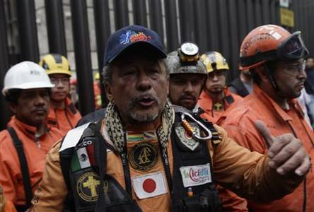 A rescue worker from the Mexican rescue team known as ''Topos'' waves to the media after leaving the headquarters of state-owned oil giant Pemex, following a deadly blast, in Mexico City February 4, 2013. Mexican rescue workers found three more bodies over the weekend amid the rubble of the deadly blast that tore through state oil firm Pemex's main office complex, the government said, as search efforts appeared to near a close.The death toll from Thursday's explosion stands at 36, Pemex said via Twitter. Rescue workers had been digging through the last sections of the building's basement and could soon call off their search. One person was reported still missing. REUTERS/Henry Romero