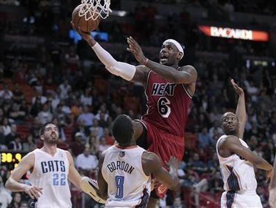 Miami Heat's LeBron James drives against Charlotte Bobcats' Byron Mullens (L), Ben Gordon (C) and Kemba Walker in the second half of their NBA basketball game in Miami, Florida February 4, 2013. REUTERS/Andrew Innerarity