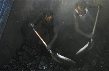 Labourers unload coal from a truck at a roadside coal store on a highway on the outskirts of Kolkata in this December 4, 2009 file photo. REUTERS/Parth Sanyal/Files