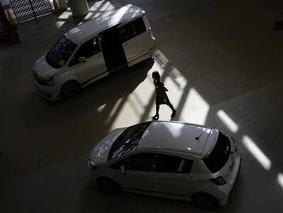 A woman walks among Toyota Motor Corp cars at the company's showroom in Tokyo February 5, 2013. REUTERS/Toru Hanai