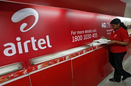 An employee checks a customers' feedback book next to a Bharti Airtel logo inside its shop in Kolkata May 2, 2012. REUTERS/Rupak De Chowdhuri