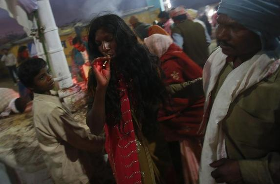 A devotee who is believed to be possessed by evil spirits smokes a bidi as she walks around the courtyard of Guru Deoji Maharaj temple during a ghost fair at Malajpur village in Betul district in Madhya Pradesh January 27, 2013. REUTERS/Danish Siddiqui