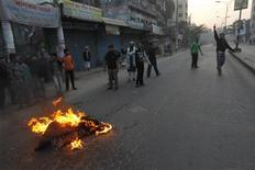 Activists of Bangladesh's Jamaat-e-Islami set fire to a blanket on a street during a day-long strike in protest against the decision by country's war crimes tribunal to deliver judgement in a case against their top leader Abdul Quader Mollah, in Dhaka February 5, 2013. A controversial war crimes tribunal sentenced a senior leader of Bangladesh's biggest Islamist party to life imprisonment on Tuesday, the second verdict in ongoing trials that have reopened old wounds about the country's bloody independence struggle. Abdul Quader Mollah was found guilty of charges including murder, rape, torture and arson during Bangladesh's war to break away from Pakistan in 1971. REUTERS/Andrew Biraj