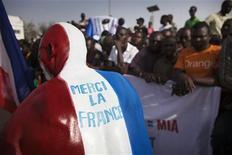 """La policía francesa arrestó el martes cerca de París a cuatro supuestos integristas islámicos dentro de una investigación sobre el reclutamiento de combatientes para los grupos relacionados con Al Qaeda en la región africana del Sahel, dijo el ministro del Interior, Manuel Valls. En la imagen del 2 de febrero se puede ver a un maliense que se ha pintado los colores de la bandera francesa en la espalda con las palabras: """"Gracias, Francia"""" antes de la visita del presidente francés, François Hollande, en la plaza de Independencia de Bamako, capital de Mali. REUTERS/Joe Penney"""