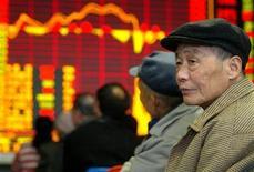 Китайские инвесторы следят за динамикой фондовых котировок в офисе брокерской конторы в Шанхае 24 марта 2004 года. Азиатские фондовые рынки, кроме Китая, снизились во вторник на фоне новых опасений по поводу еврозоны. REUTERS/Claro Cortes IV