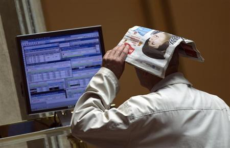 A trader covers his head with a newspaper as he checks a trading screen at the Madrid Bourse May 16, 2012. REUTERS/Sergio Perez/Files