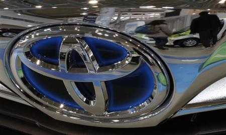 A visitor walking past cars is reflected on a Toyota car at the company's showroom in Tokyo February 5, 2013.