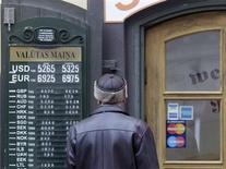 Мужчина смотрит курсы валют у обменного пункта в Риге 3 января 2013 года. Евро вернулся к росту после выхода неожиданно высоких макроэкономических показателей еврозоны. REUTERS/Ints Kalnins