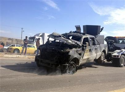 A police vehicle is towed after a suicide bomb attack in Taji, 20 km (12 miles) north of Baghdad Febraury 5, 2013. REUTERS/Mohammed Ameen