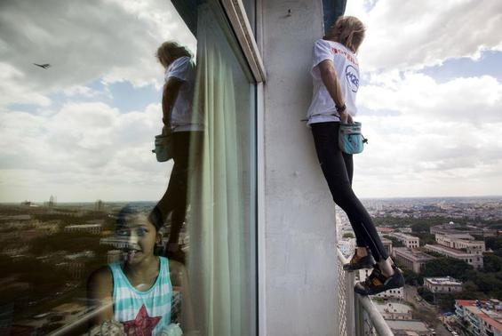 Alain Robert of France, who is known as 'Spiderman', climbs up the Habana Libre hotel as a youth looks out a window in Havana February 4, 2013. Robert, who scales buildings all over the world without safety equipment, successfully climbed the hotel which is 413 feet high. REUTERS/Ramon Espinosa/Pool