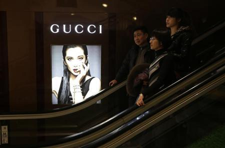 Customers ride an escalator next to a Gucci advertisement in a shopping mall in Wuhan, Hubei province, January 19, 2013. REUTERS/Stringer