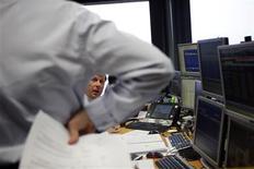 La escalada de la prima de riesgo española de los últimos días por la irrupción de un escándalo político encarecerá la financiación del país cuando esta semana emita tres referencias de deuda pública a la vez que la demanda será sólida. En la imagen, varios agentes de Inversis durante una subasta de bonos en Madrid el 10 de enero de 2013. REUTERS/Susana Vera