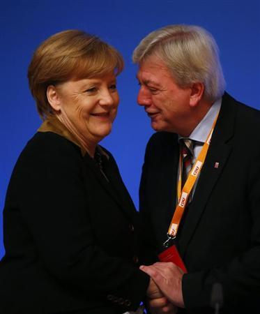 German Chancellor and leader of Germany's Christian Democratic Union (CDU), Angela Merkel and Hesse's Prime Minister Volker Bouffier acknowledge the applause of the delegates after her speech at the CDU's annual party meeting in Hanover, December 4, 2012.