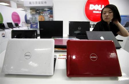A Chinese saleswoman stands behind a row of Dell computers at a computer market in Beijing June 29, 2009. REUTERS/David Gray/Files