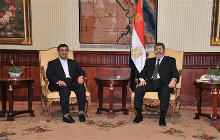 Egyptian President Mohamed Mursi (R), meets with Iran's President Mahmoud Ahmadinejad after he arrived at International Airport in Cairo in this photo provided by the Egyptian Presidency on February 5, 2013. REUTERS/Egyptian Presidency/Handout